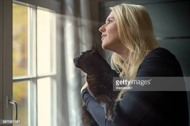 Woman and her cat looking through the window at home