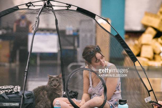 Woman and her cat rest inside a tent at the Oregon Convention Center cooling station in Oregon, Portland on June 28 as a heatwave moves over much of...