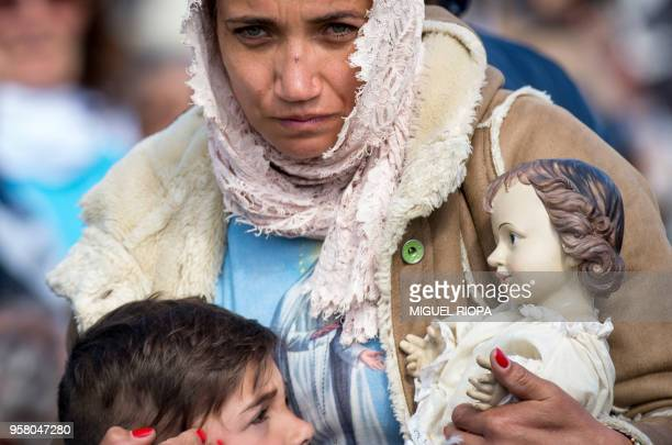 TOPSHOT A woman and her child attend a mass ceremony at the Fatima shrine in Fatima central Portugal on May 13 2018 Thousands of pilgrims converged...