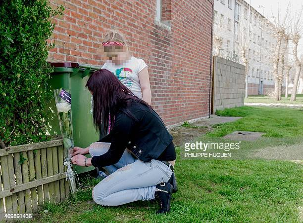 A woman and her child lay flowers on April 16 2015 where a nineyearold girl was snatched on April 15 in front of her mother from a playground in the...