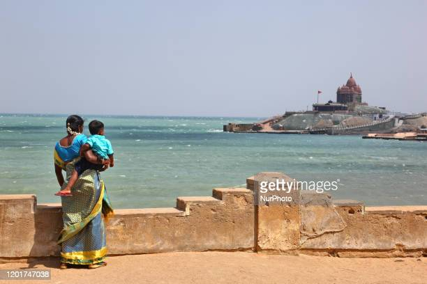 Woman and her child look out towards the Vivekananda Rock Memorial temple seen on a small island in the ocean in Kanyakumari Tamil Nadu India