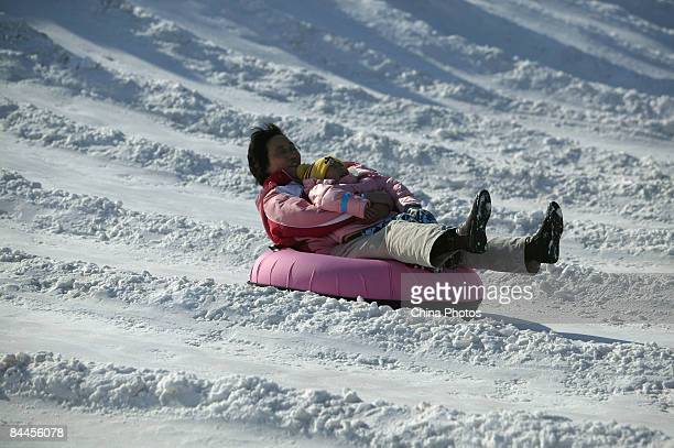 A woman and her child play at the Snow Carnival at the Olympic Forest Park on January 26 2009 in Beijing China The Ox which has been ushered in today...