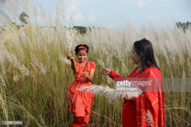 Woman and her child playing with flowers at Kans grass field in Sarighat, on the outskirts of Dhaka. Kans grass field in Sarighat is one of the...