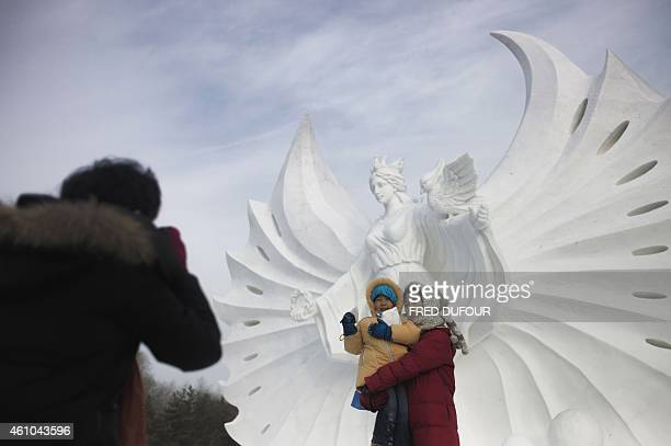 A woman and her child poses in front a snow sculpture during the 16th Harbin International Ice and Snow Festival in Harbin northeast China's...