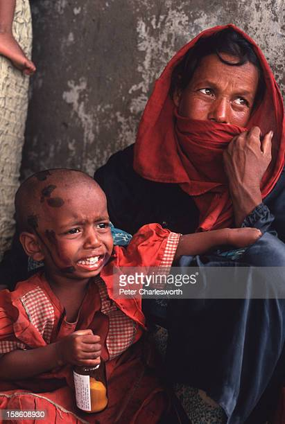A woman and her child sit in a cyclone shelter waiting for emergency relief after surviving one of the biggest cyclones to hit Bangladesh in recent...
