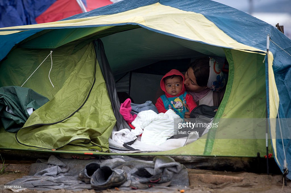 A woman and her child sit in her tent at the Idomeni refugee camp on the Greek Macedonia border on March 14, 2016 in Idomeni, Greece. The decision by Macedonia to close its border to migrants last Wednesday has left thousands of people stranded at the Greek transit camp. The closure, following the lead taken by neighbouring countries, has effectively sealed the so-called western Balkan route, the main migration route that has been used by hundreds of thousands of migrants to reach countries in western Europe such as Germany. Humanitarian workers have described the conditions at the camp as desperate, which has been made much worse by recent bouts of heavy rain.