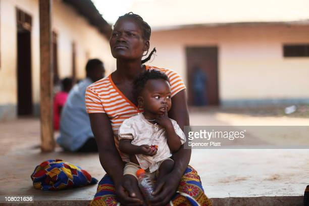 A woman and her child sit in the courtyard of a hospital that is run in partnership with Doctors Without Borders January 13 2011 in the town of...