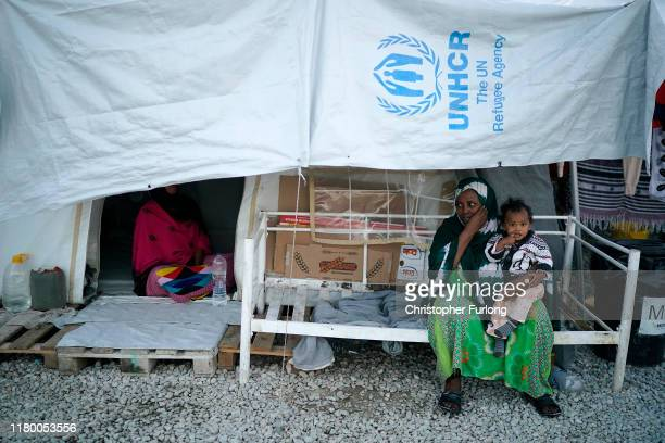 A woman and her child sit in the Moria migrant camp which was built for 3000 people but now contains over 13000 on October 09 2019 in Mytilene Greece...