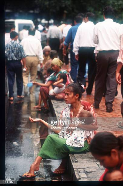 A woman and her child sits on the street begging for money January 1999 in Jakarta Indonesia Religious and ethnic tensions mount between a largely...