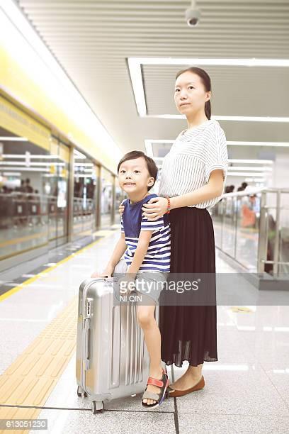 Femme et son enfant en attente de la gare ferroviaire