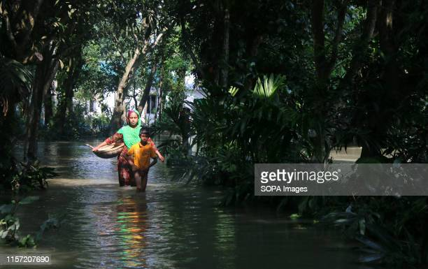 A woman and her child walk in a flood affected area following heavy monsoon rains at a flood affected area in Tangail Over million people have been...