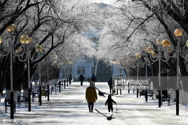 A woman and her child walk in an alley of snowcovered trees in Baikonur city near the Russian leased Kazakh Baikonur cosmodrome on December 13 2017...