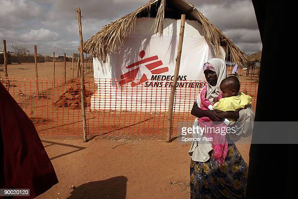 A woman and her child walk past a tent for a Doctors Without Borders medical station in Dadaab the world�s biggest refugee complex August 22 2009 in...