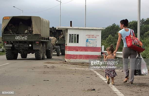 A woman and her child walk toward the Georgianabkhazian border as Russian troops withdraw on August 22 in western Georgia About 80 vehicles including...
