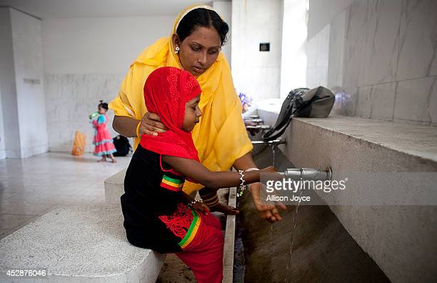 A woman and her child wash before praying at the National Mosque Baitul Mukarram during Eid alFitr on July 29 2014 in Dhaka Bangladesh Muslims around...