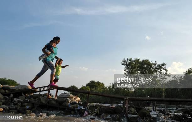 "Woman and her children cross from San Antonio del Tachira, in Venezuela, to Cucuta, in Colombia, through ""trochas"" -illegal trails- near the Simon..."