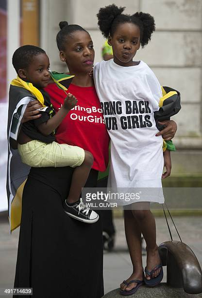 A woman and her children look on during a demonstration outside the Nigerian Embassy in Central London on May 17 calling for the release of...