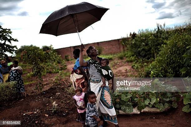 A woman and her children stand under an umblella in Lilongwe on March 14 2016 / AFP / ARIS MESSINIS / RESTRICTED TO EDITORIAL USE