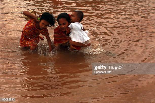 A woman and her children struggle to cross a waterway July 25 2008 in the port city of Chittagong Bangladesh Bangladesh the most crowded nation on...