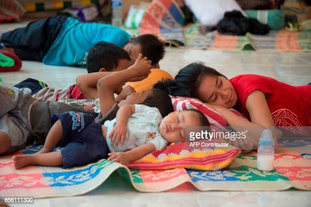 A woman and her children take a nap at an evacuation shelter in Tembok Buleleng Regency on the Indonesian resort island of Bali on October 1 2017...