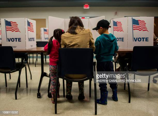 TOPSHOT A woman and her children vote at a polling station during the midterm elections at the Fairfax County bus garage in Lorton Virginia on...