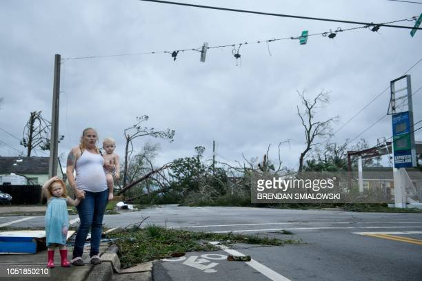 TOPSHOT A woman and her children wain near a destroyed gas station after Hurricane Michael in Panama City Florida on October 10 2018 Michael slammed...