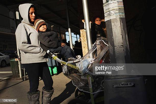 A woman and her children wait in line to receive free milk from the Milk from the Heart program which makes weekly deliveries to Washington Heights...
