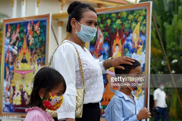 Woman and her children, wearing face masks as a preventive measure against the spread of the COVID-19 novel coronavirus, attend the Visak Bochea...