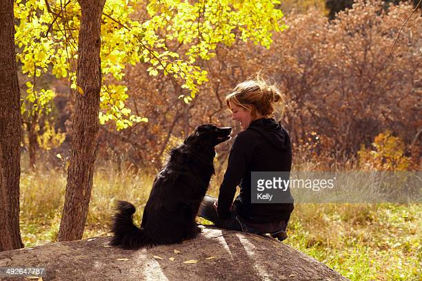 woman and her collie sitting on stone, colorado, usa - collie stock photos and pictures