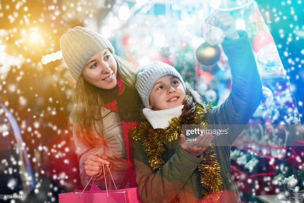 Woman and her daughter are preparing for Christmas and choosing : Stock Photo