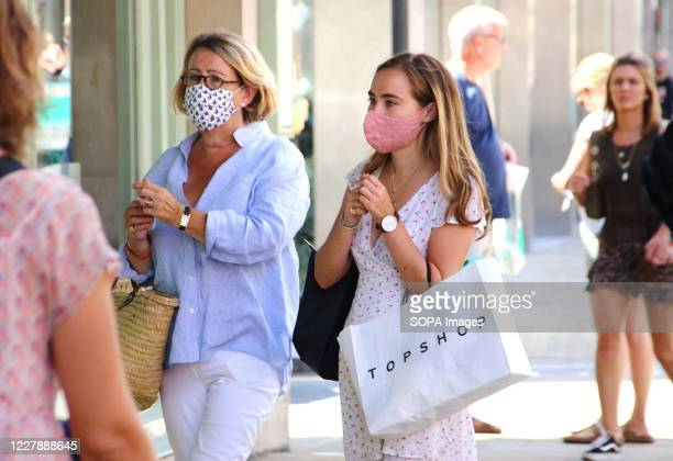 Woman and her daughter are seen about to enter a shop with their facemasks on as a preventative measure against Covid-19. Face masks must now be worn...