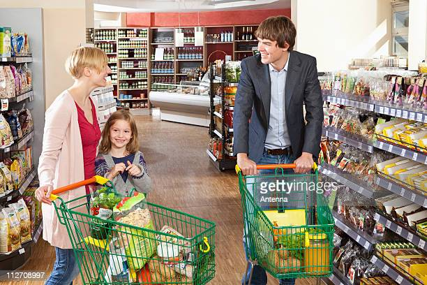 A woman and her daughter chatting with a man in a supermarket