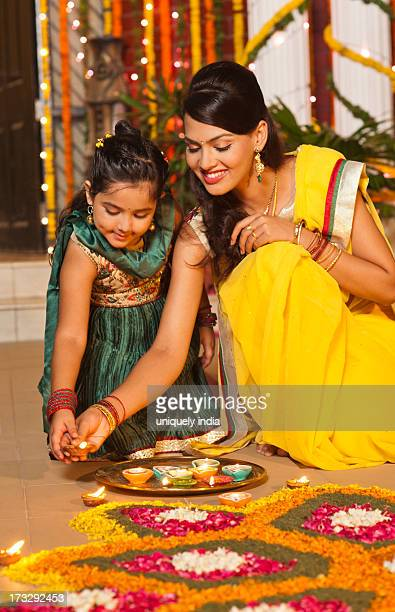 Woman and her daughter decorating rangoli with oil lamps on Diwali