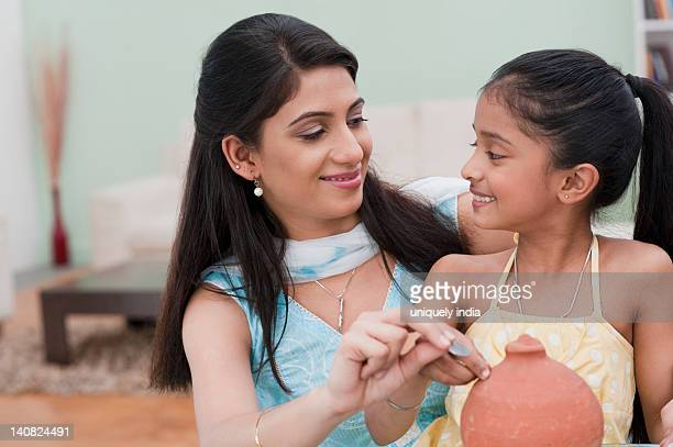 Woman and her daughter inserting a coin into a piggy bank