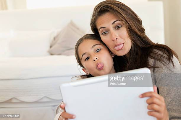 Woman and her daughter making their faces in front of digital tablet
