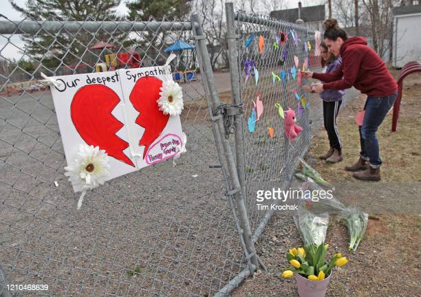 A woman and her daughter place a heart on a fence at a growing memorial in front of the Debert School April 20 2020 in Debert Nova Scotia Canada Lisa...