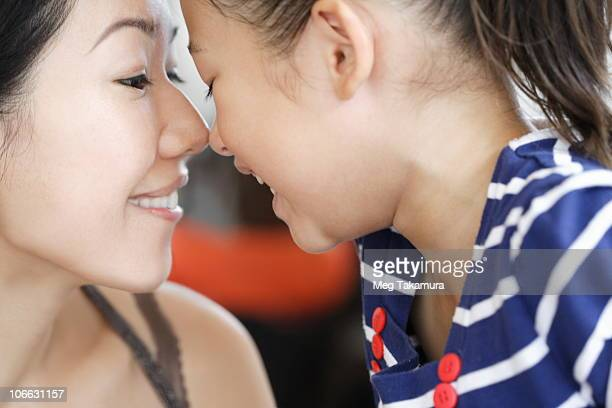 Woman and her daughter rubbing noses