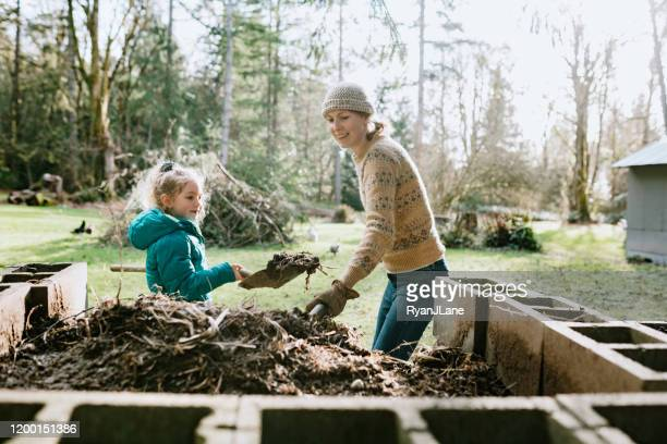 woman and her daughter shoveling compost into wheelbarrow - female mound stock pictures, royalty-free photos & images