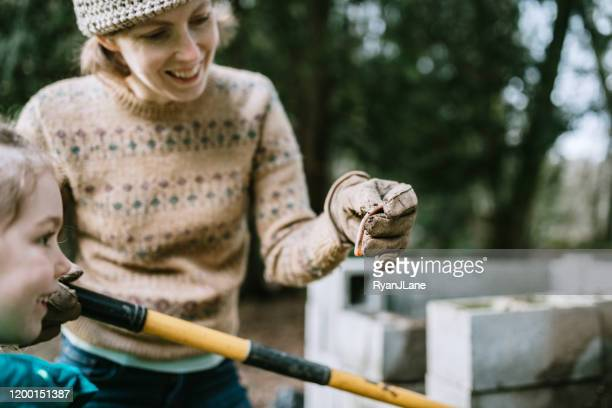woman and her daughter shoveling compost into wheelbarrow - earthworm stock pictures, royalty-free photos & images