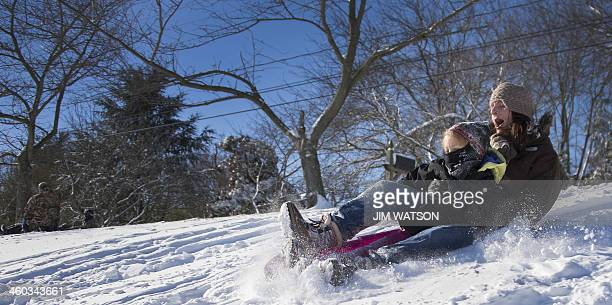 A woman and her daughter sled down a hill in Centreville Maryland on January 3 after the first snow of the new year hit Maryland A fierce winter...