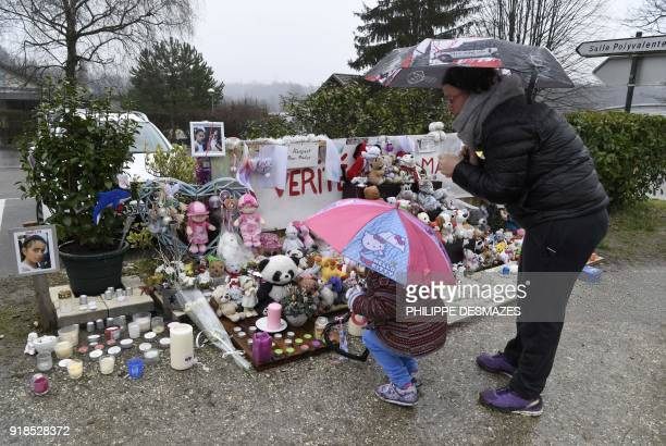 TOPSHOT A woman and her daughter stand in front of candles toys and messages displayed in tribute to eightyearold Maelys de Araujo on February 15 in...