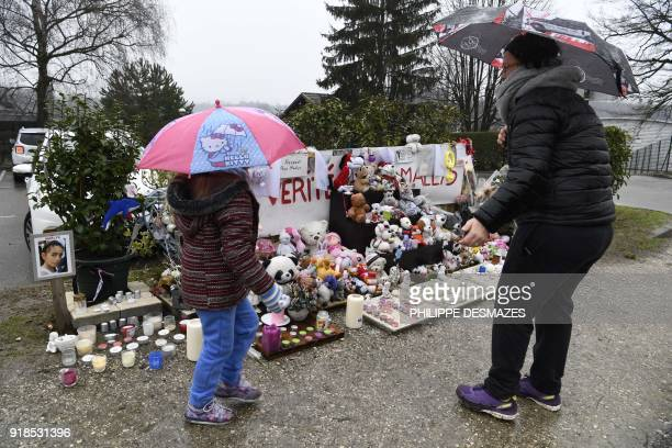 A woman and her daughter stand in front of candles toys and messages displayed in tribute to eightyearold Maelys de Araujo on February 15 in Le...