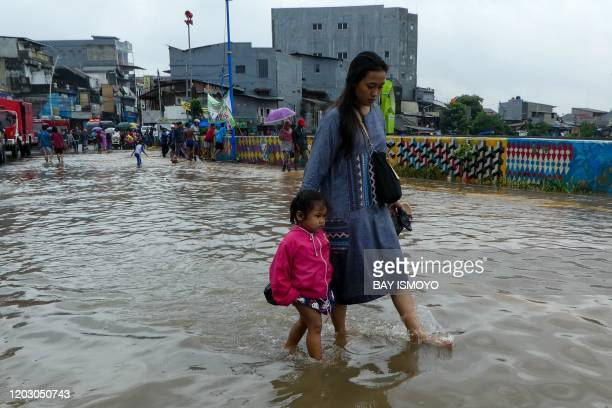 Woman and her daughter walk through a flooded road after heavy rain in Jakarta on February 25, 2020. - Dozens of Jakarta neighbourhoods were flooded...