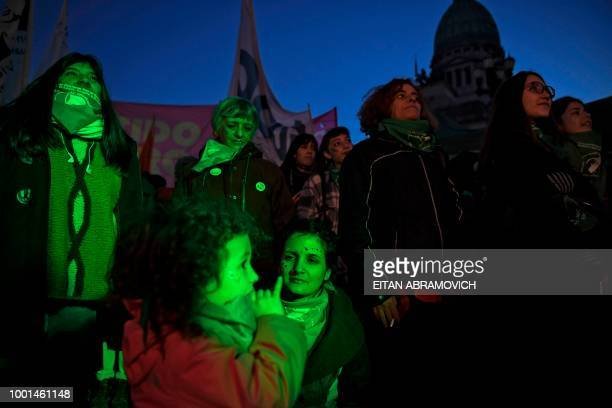 A woman and her daughter wear green headscarves as they attend a rally in favor of the legalization of abortion outside the Congress building in...