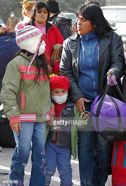A woman and her daughters using a mask to protect themselves from ashes prepare to board during evacuation operations by the Chilean Navy following...