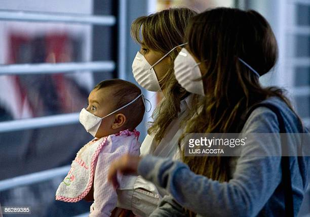 A woman and her daughters wear masks in an attempt to prevent contagion of the swine flu at the International Airport of Mexico City on April 29 2009...