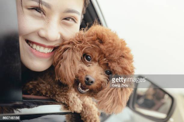 woman and her dog in car blowing in the wind