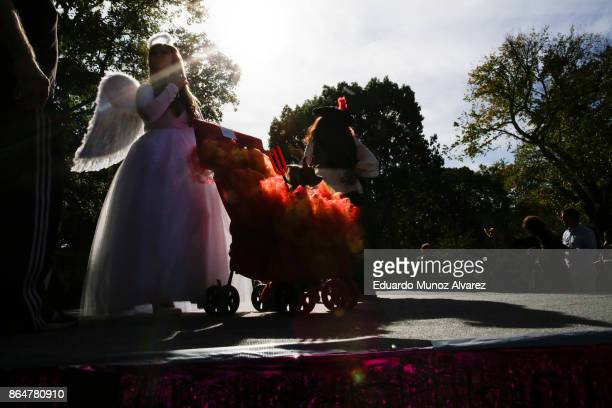 Woman and her dog in costumes attend the 27th Annual Tompkins Square Halloween Dog Parade in Tompkins Square Park on October 21, 2017 in New York...