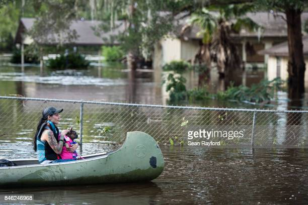 A woman and her dog navigate floodwaters caused by Hurricane Irma on September 12 2017 in Middleburg Florida United States The storm brought flooding...