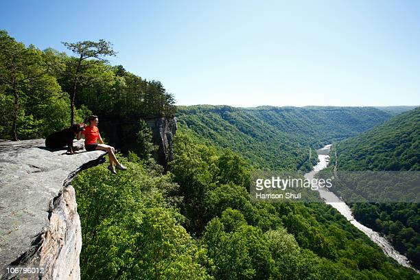 Woman and her dog take in the view from a high mountain cliff.